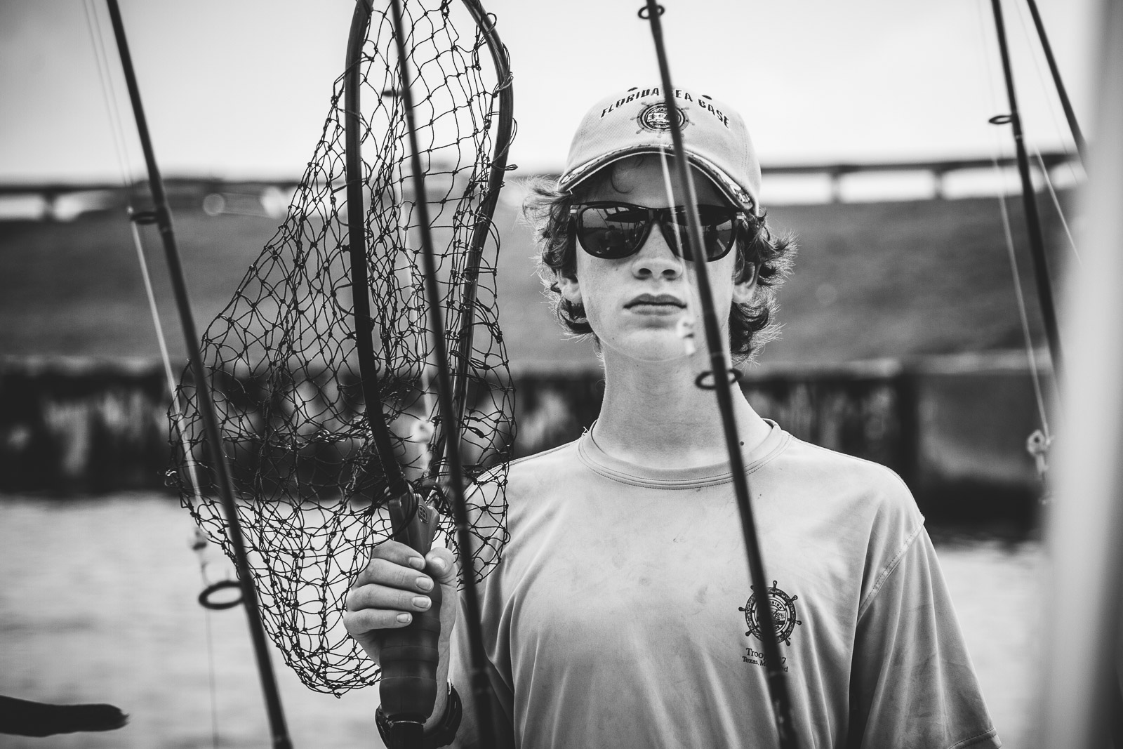 A boy holding a fishing pole in a still black and white photo during a video fusion photo session