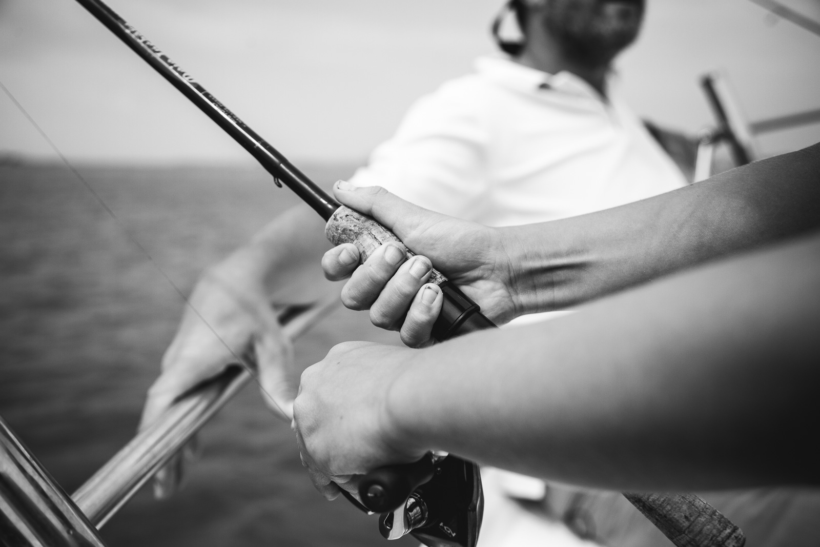 Hands on a fishing rod in a still black and white photo during a video fusion photo session