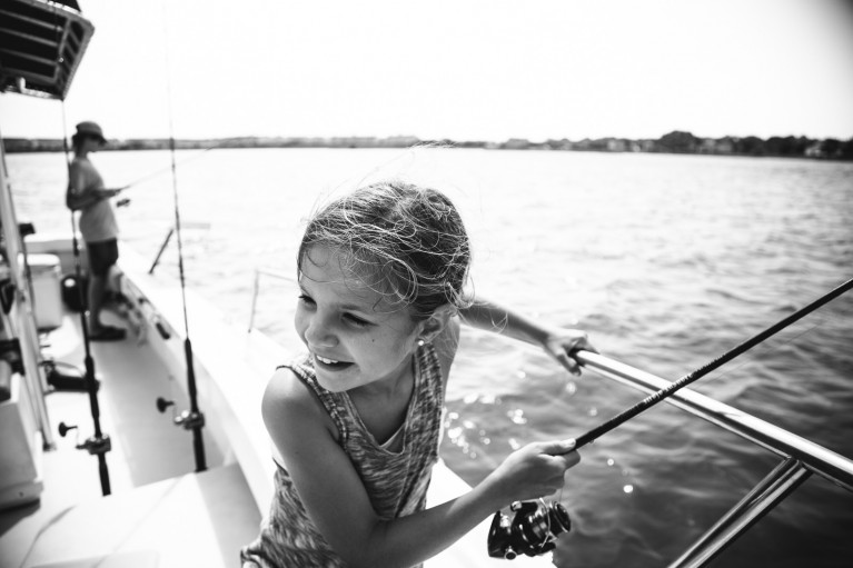 A girl fishing in a still black and white photo during a video fusion photo session