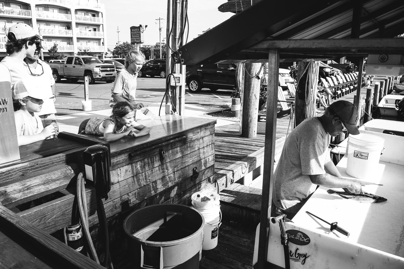 Black and white photo of people cleaning fish during a family photo session