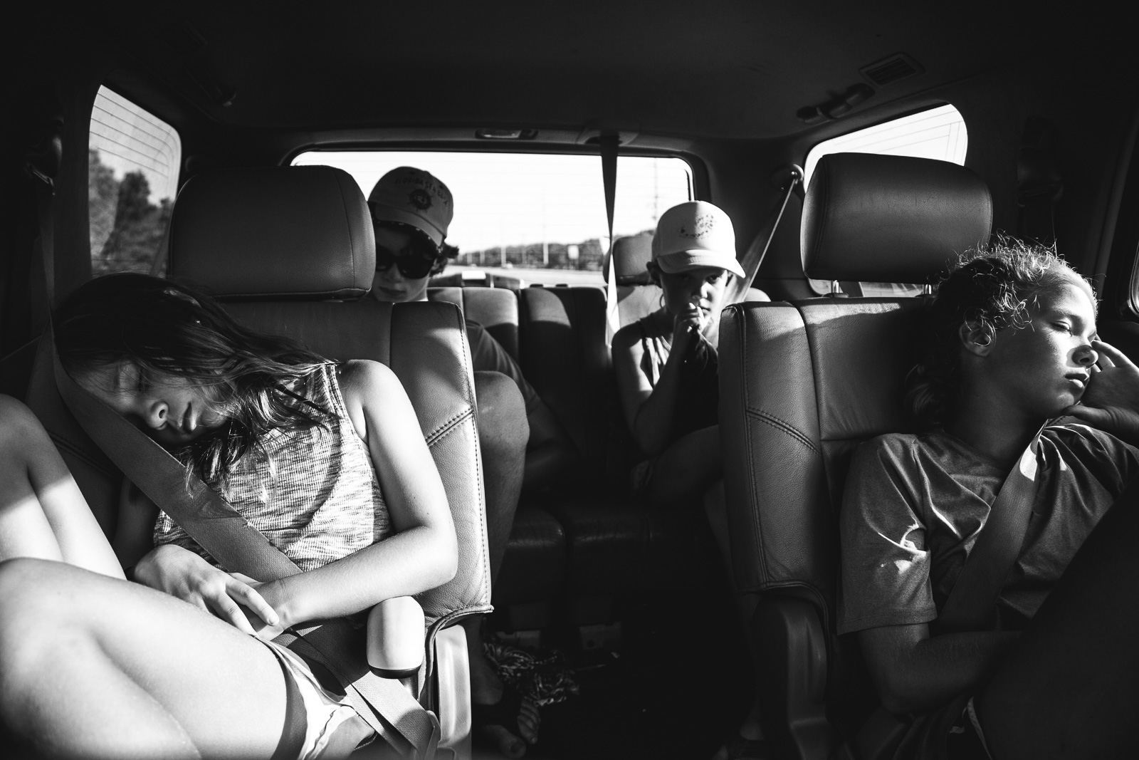 Kids sleeping in the back of a mini van after a photo session