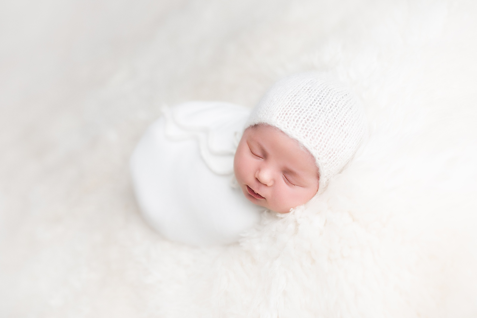 A swaddled newborn in a back-lying pose.