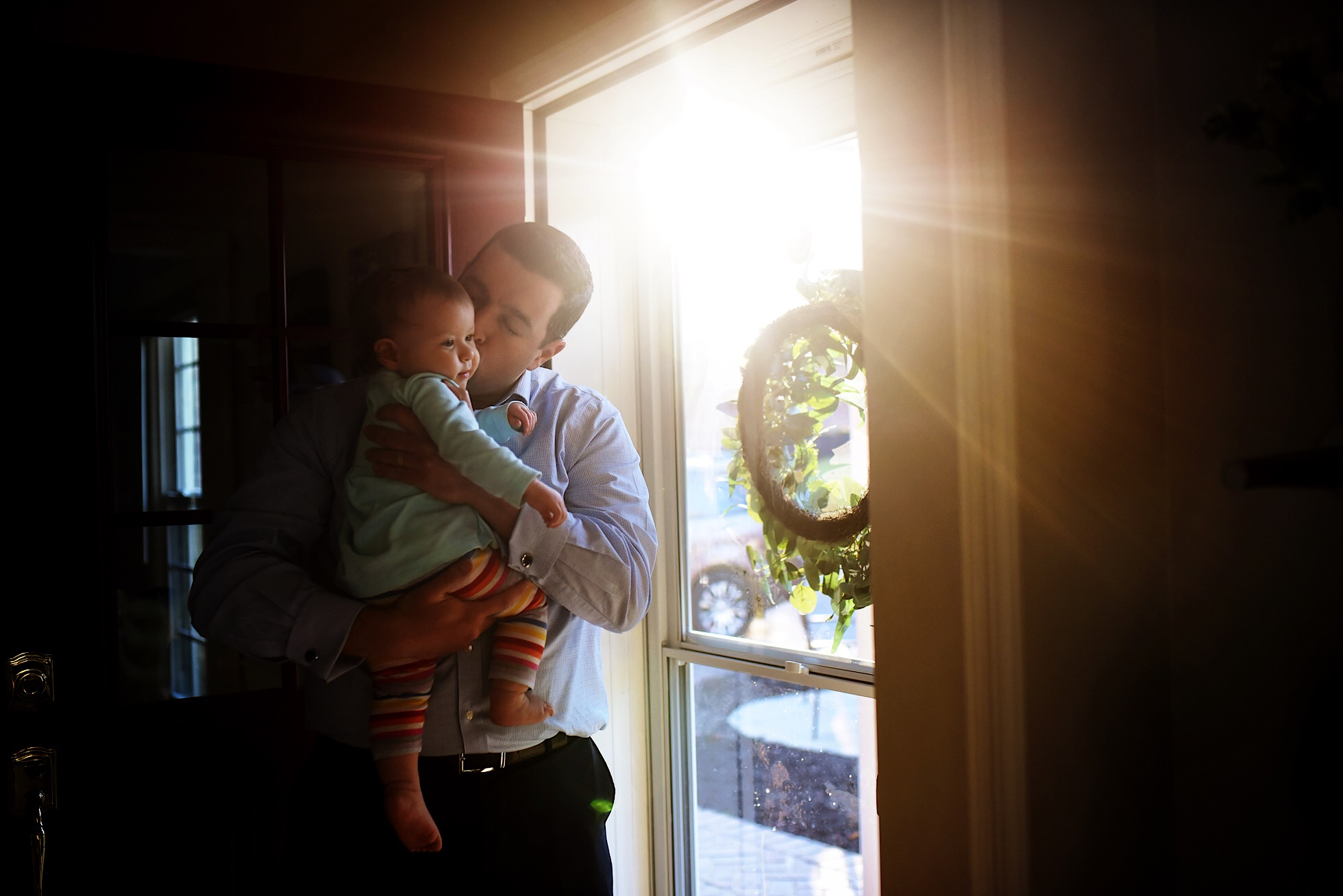 A dad kisses his baby