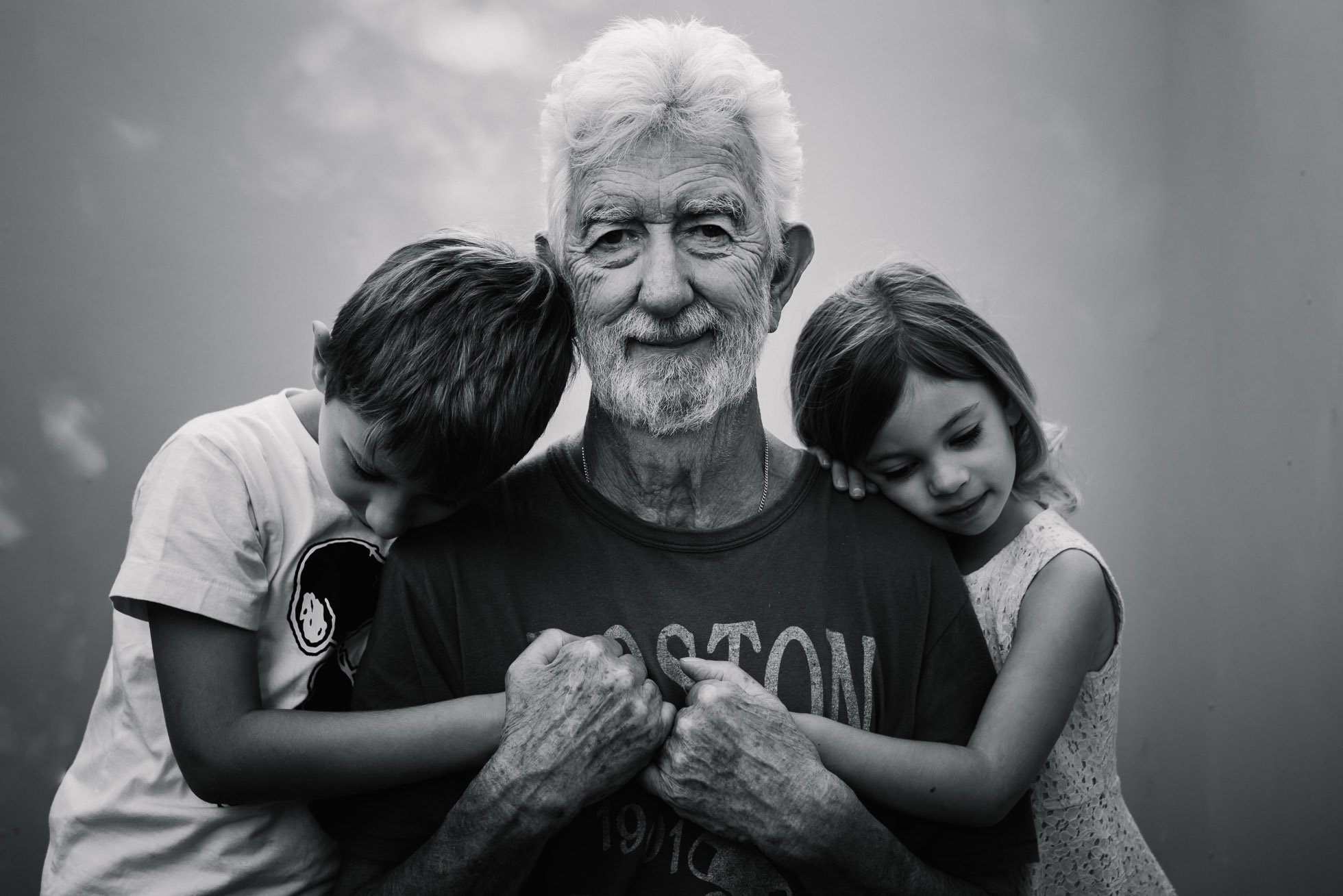 a grandfather hugs his grandchildren