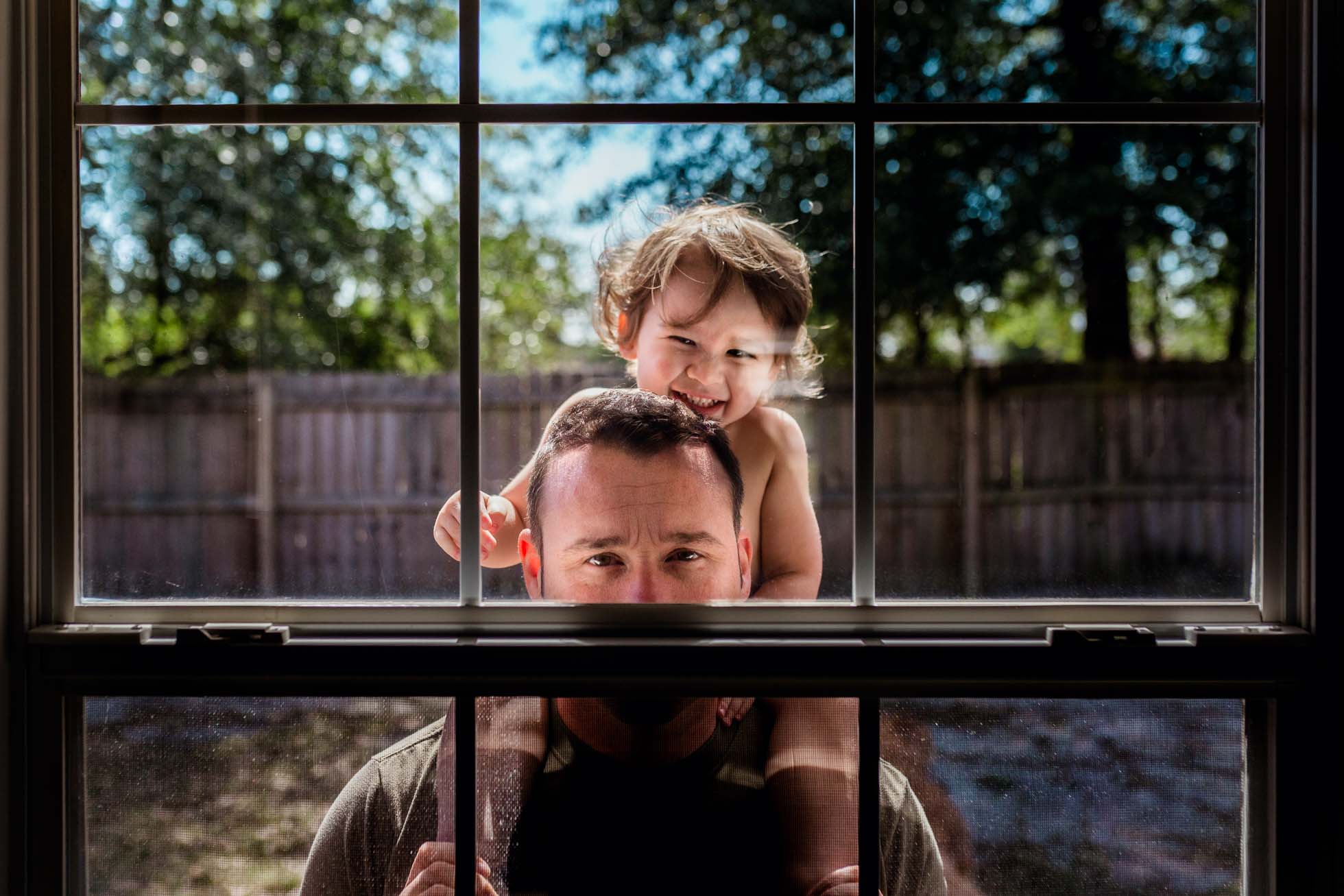 A dad and his son look through a window