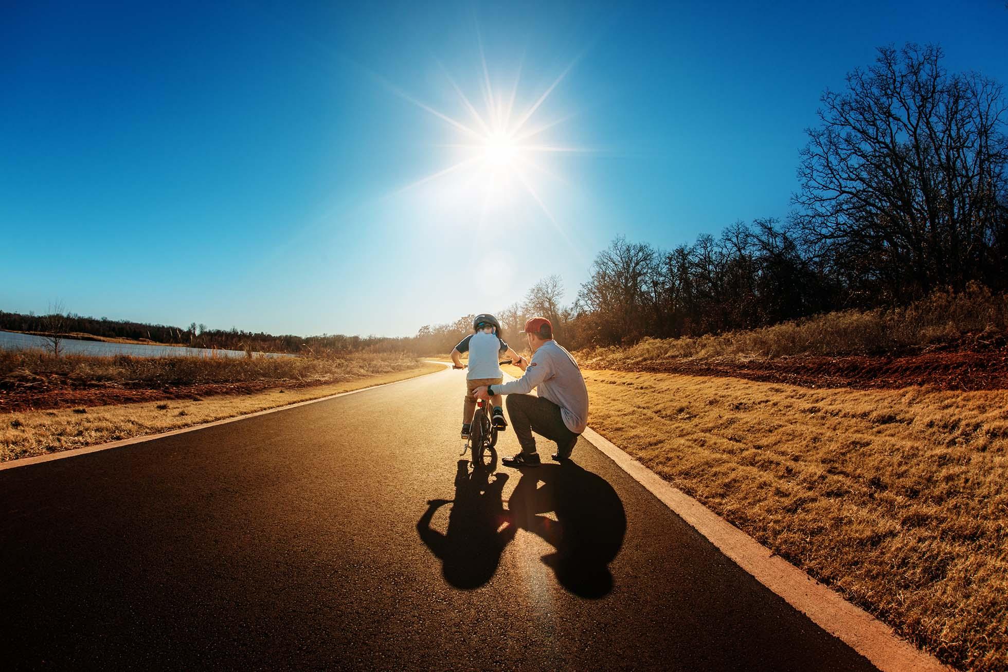 A dad teaches his son to ride a bike