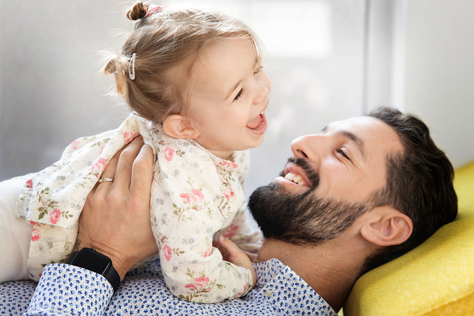 A dad holds his laughing daughter