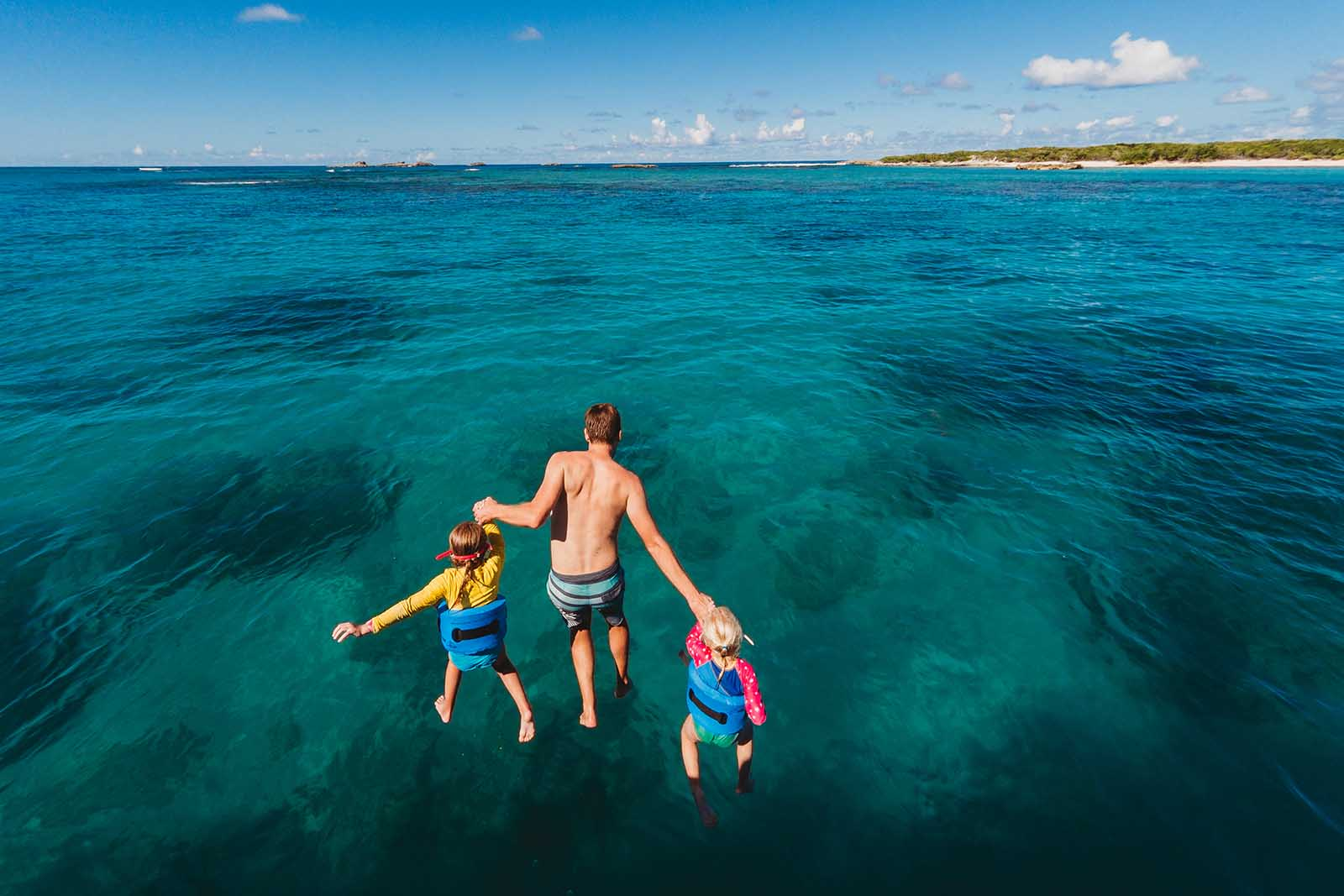 Kids jumping into the ocean with their dad - color in photos