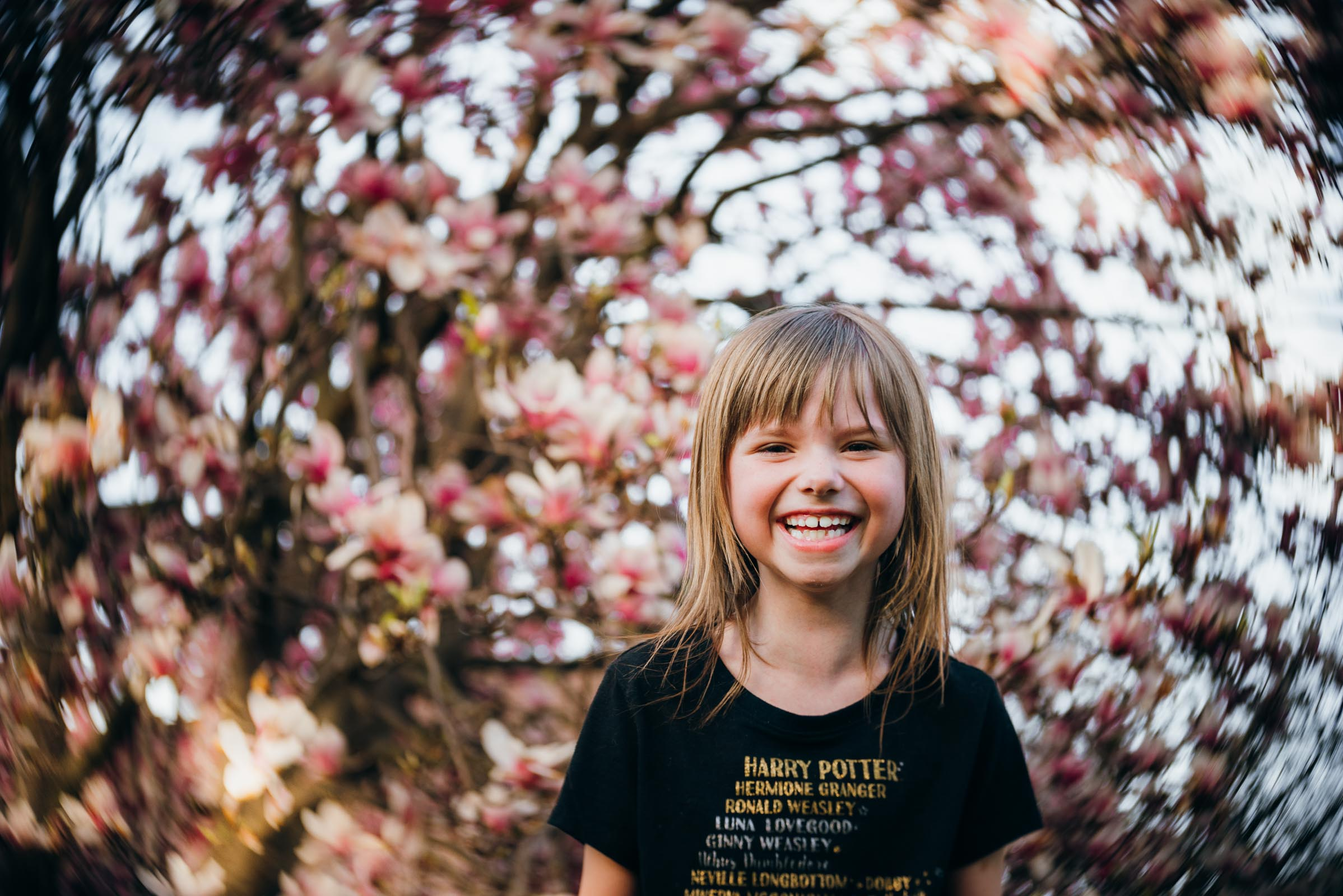 Girl smiling with magnolia tree, lensbaby