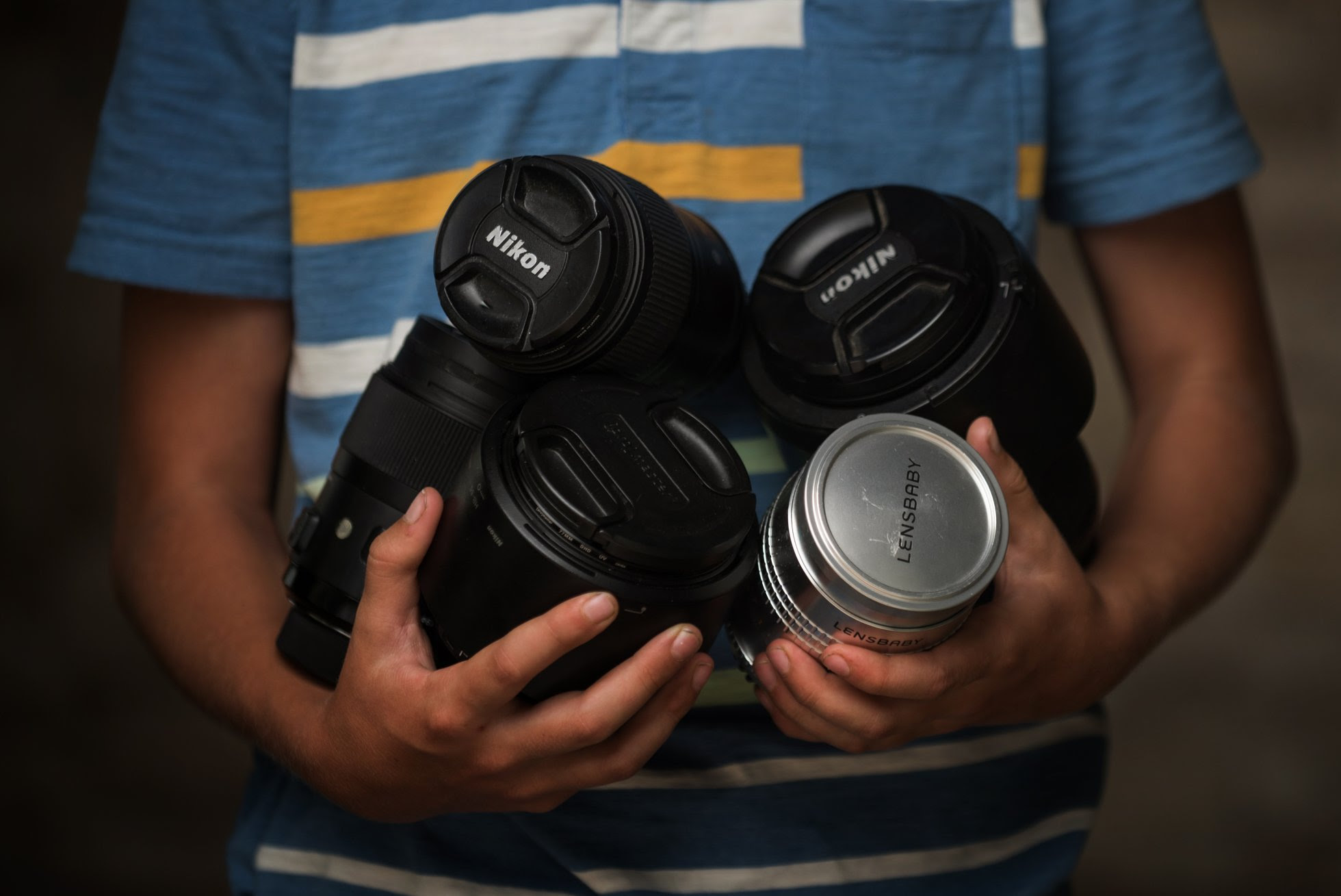 Boy holding photography lenses - how to buy a camera