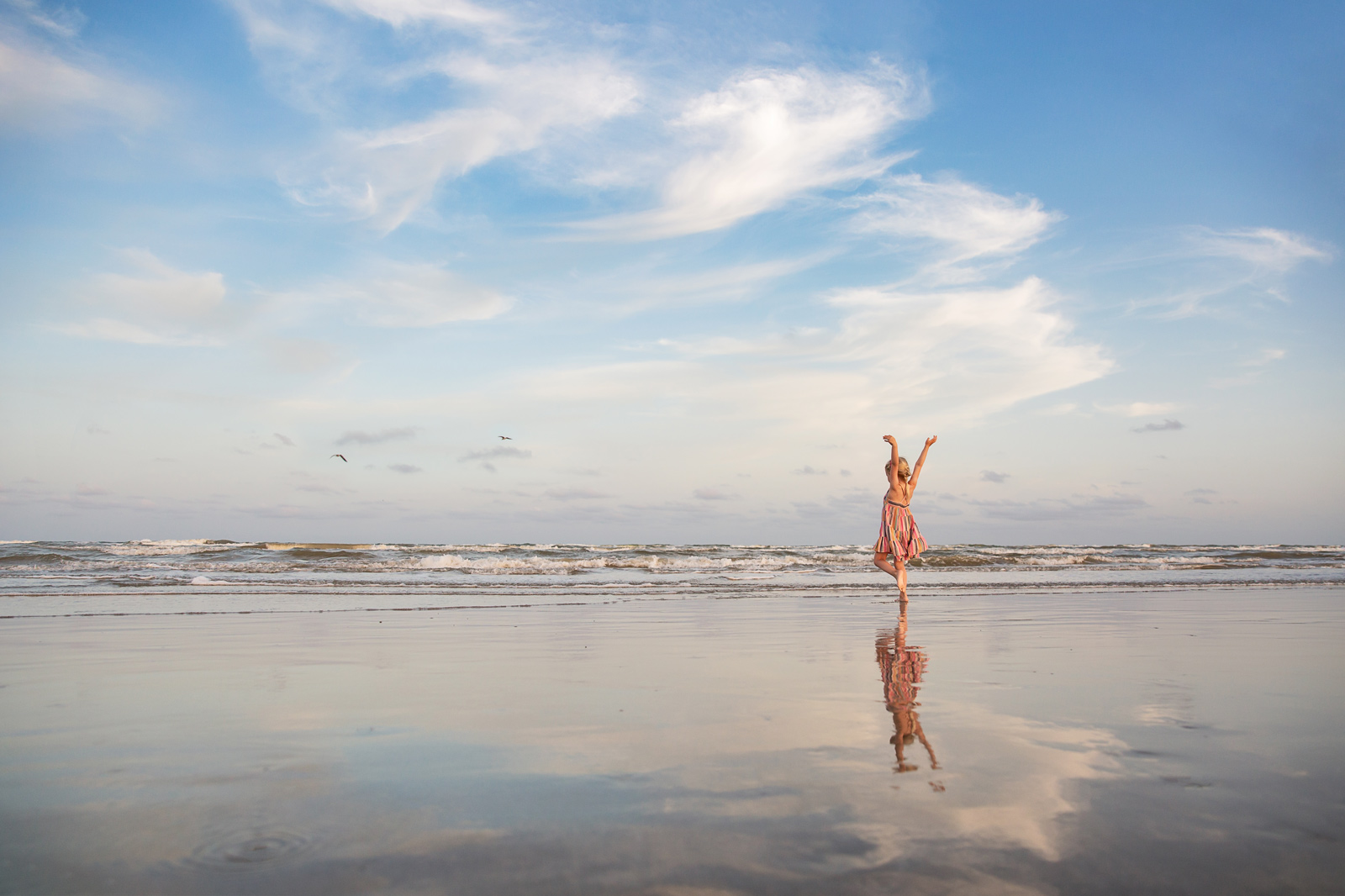 Girl dancing at beach with dramatic sky behind her