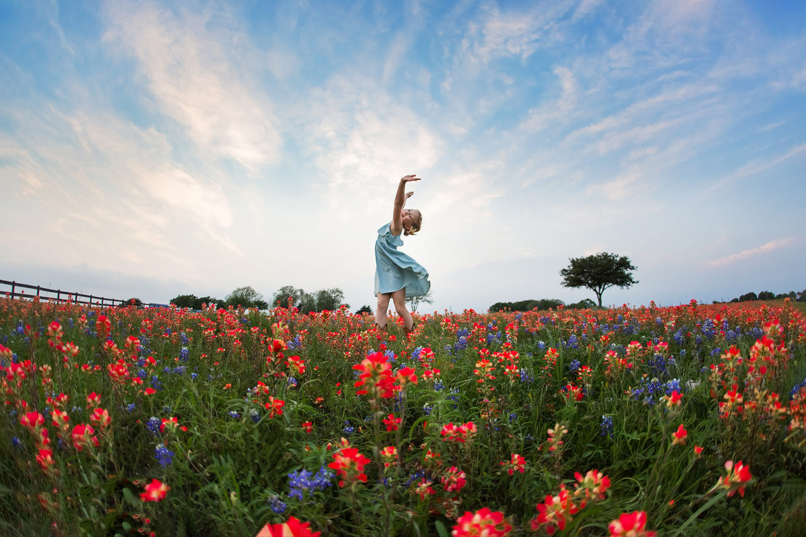 Girl dancing in tulip field with dramatic blue sky background