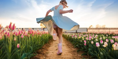 Girl running through tulip field with dramatic blue sky background