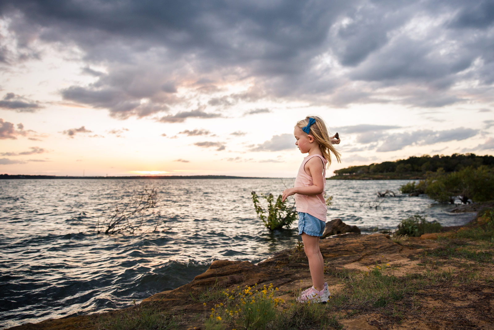 Girl throwing rock in front of properly exposed dramatic sky