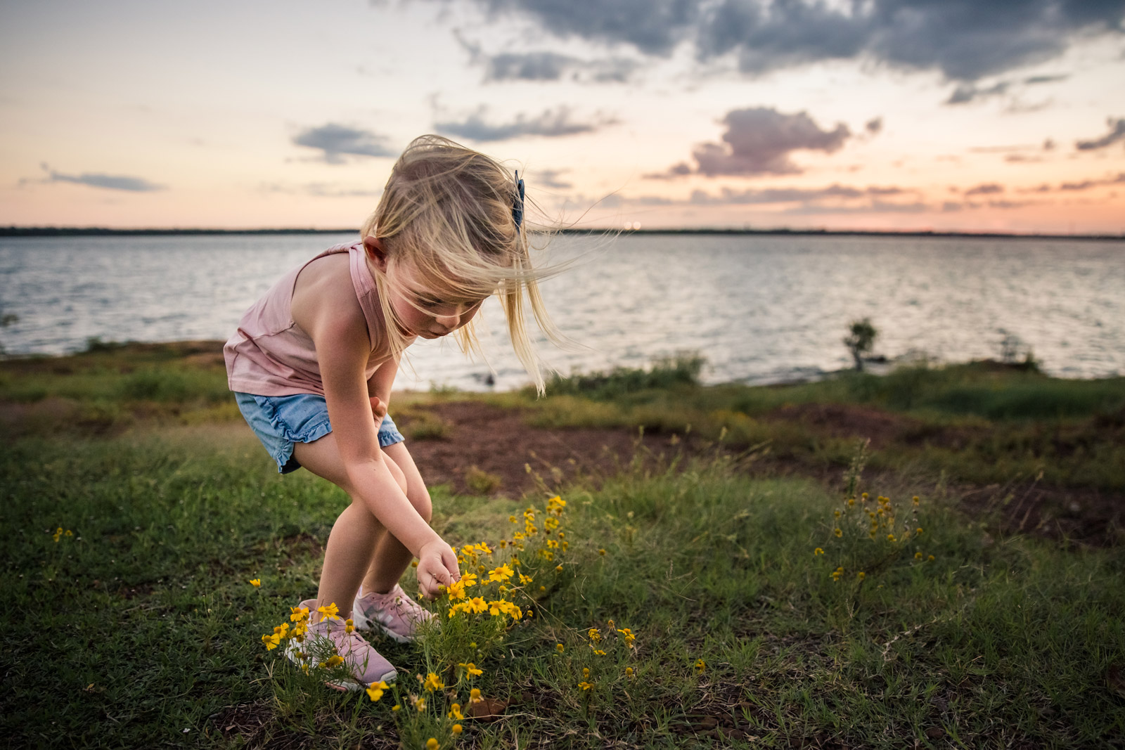Girl picking flowers in front of dramatic sky photo