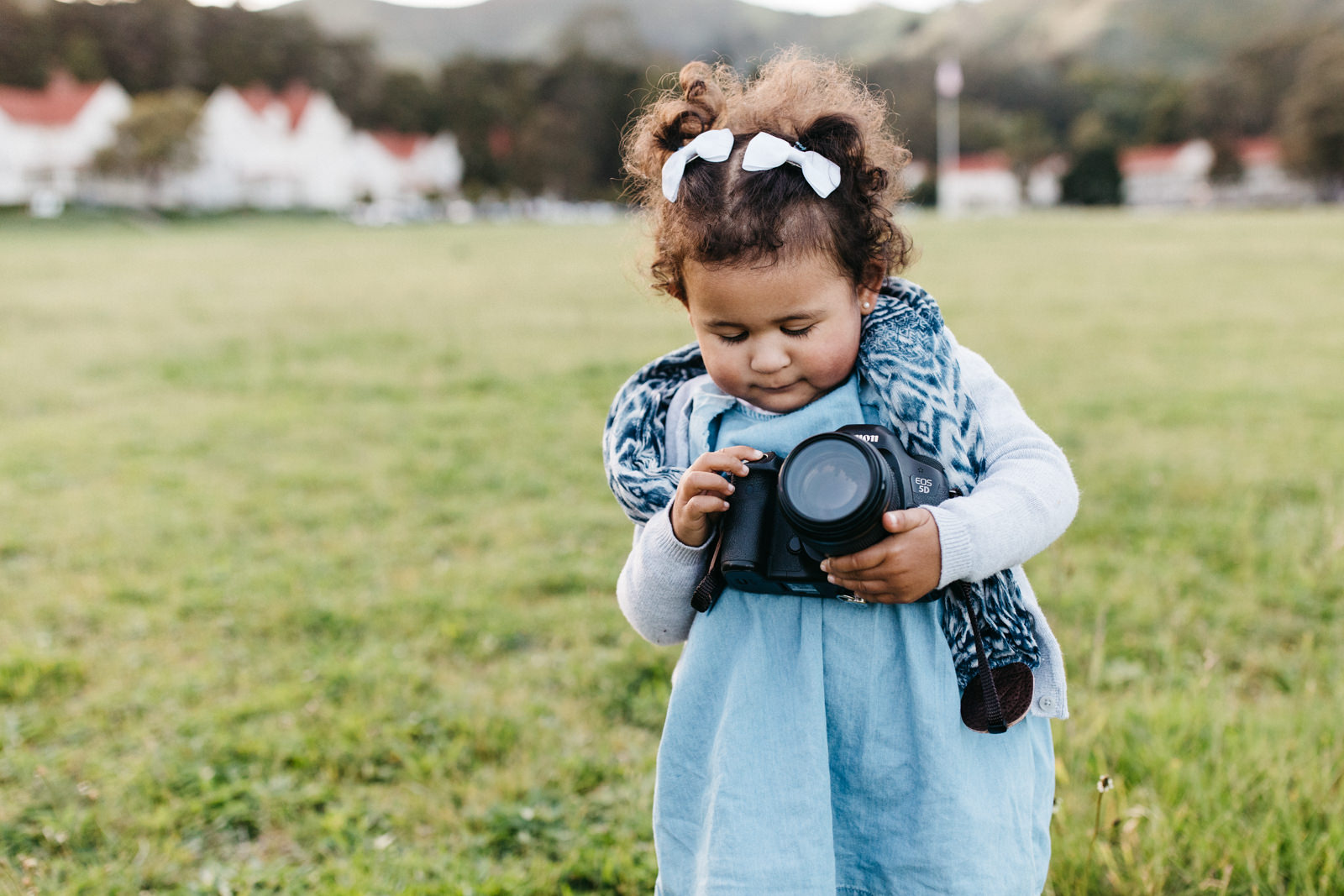 Little girl holding big camera - Photographing shy kids