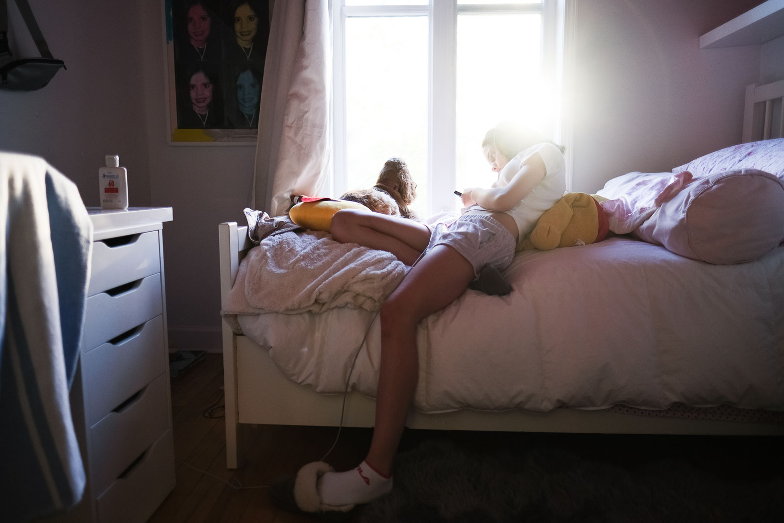 Girl texting on a bed in strong light: how to build a photography portfolio