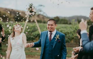 Confetti is thrown as couple walks down aisle at wedding
