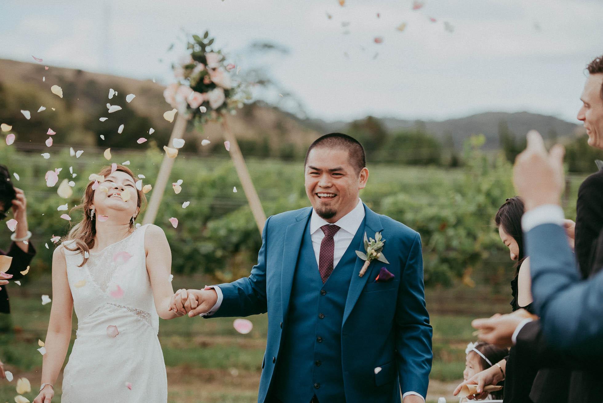 Confetti is thrown as couple walks down aisle at wedding