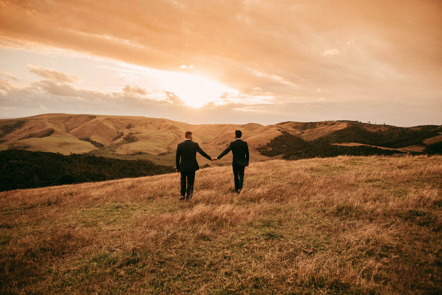Two grooms walk together at sunset