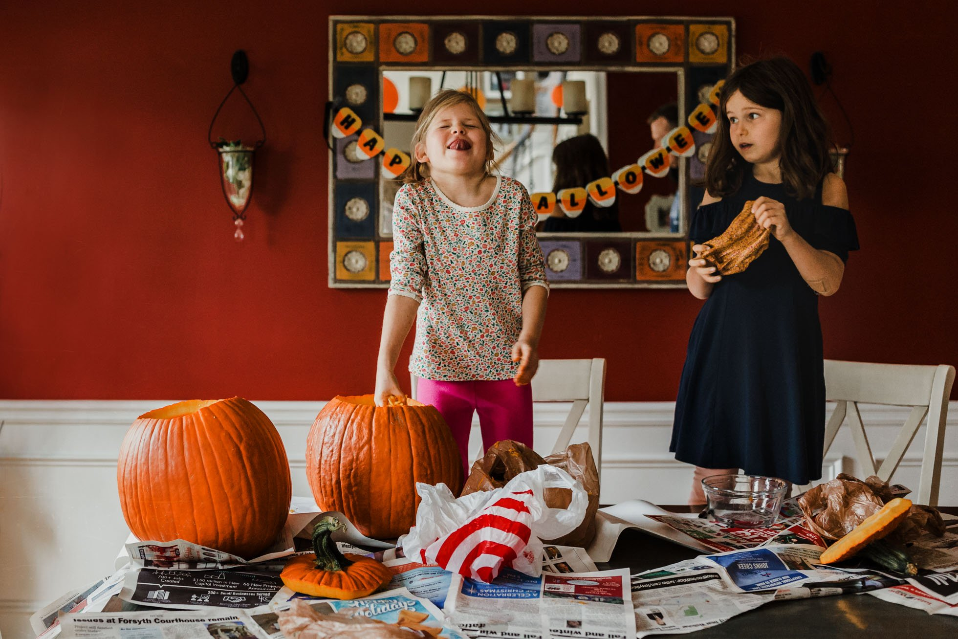 Girls carving pumpkins at home before Halloween