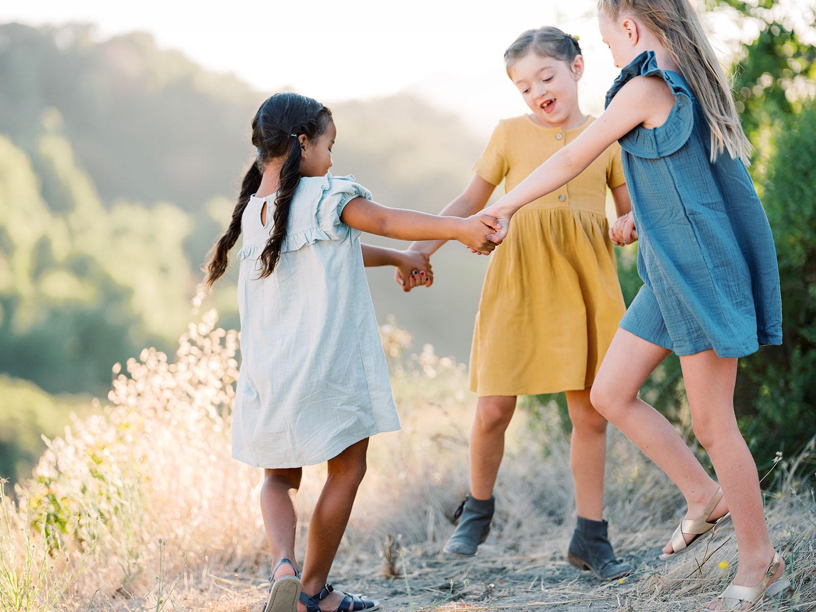 Girls spinning on hillside, movement