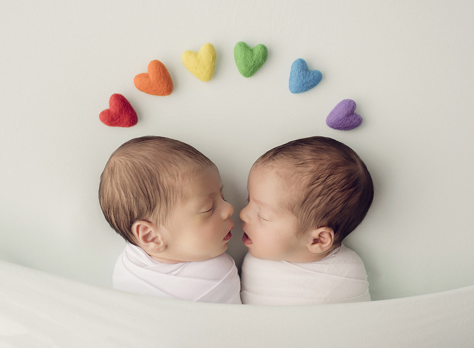 Rainbow baby photos of twins with colorful hearts