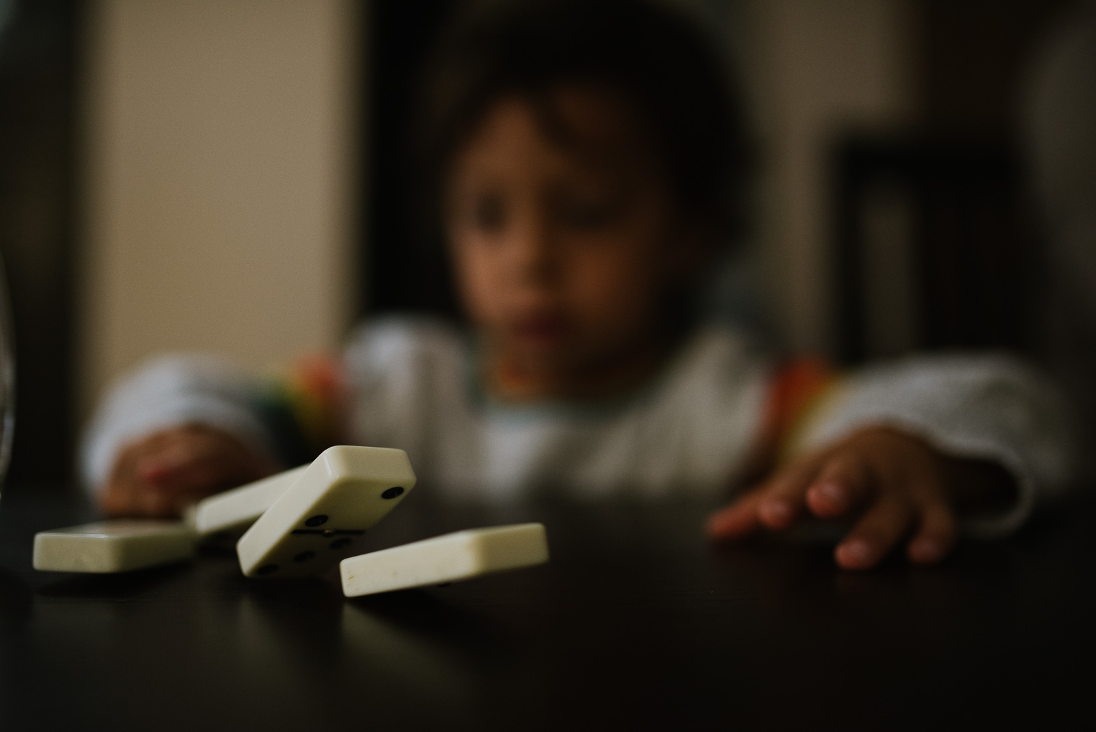 Freezing motion in photography, dominoes fall as a child plays