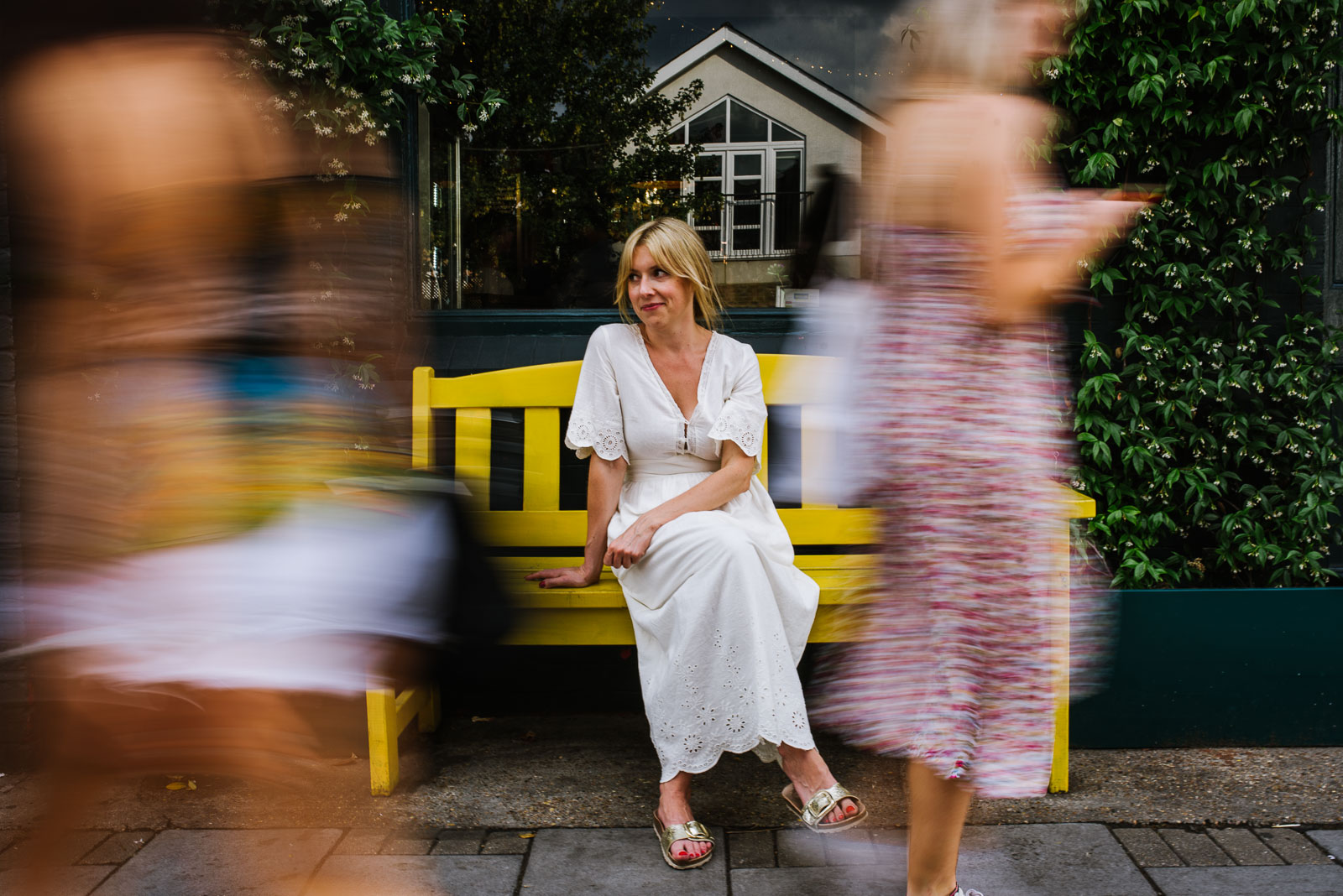 Motion blur of a woman still on a bench while people walk by