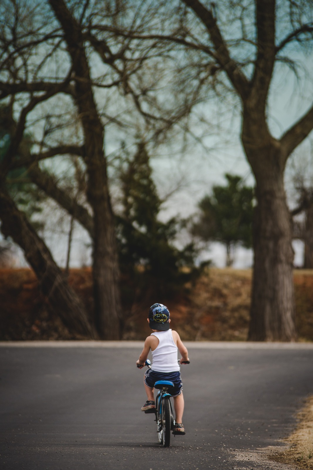 A boy rides away on a bike, taking a break from photography