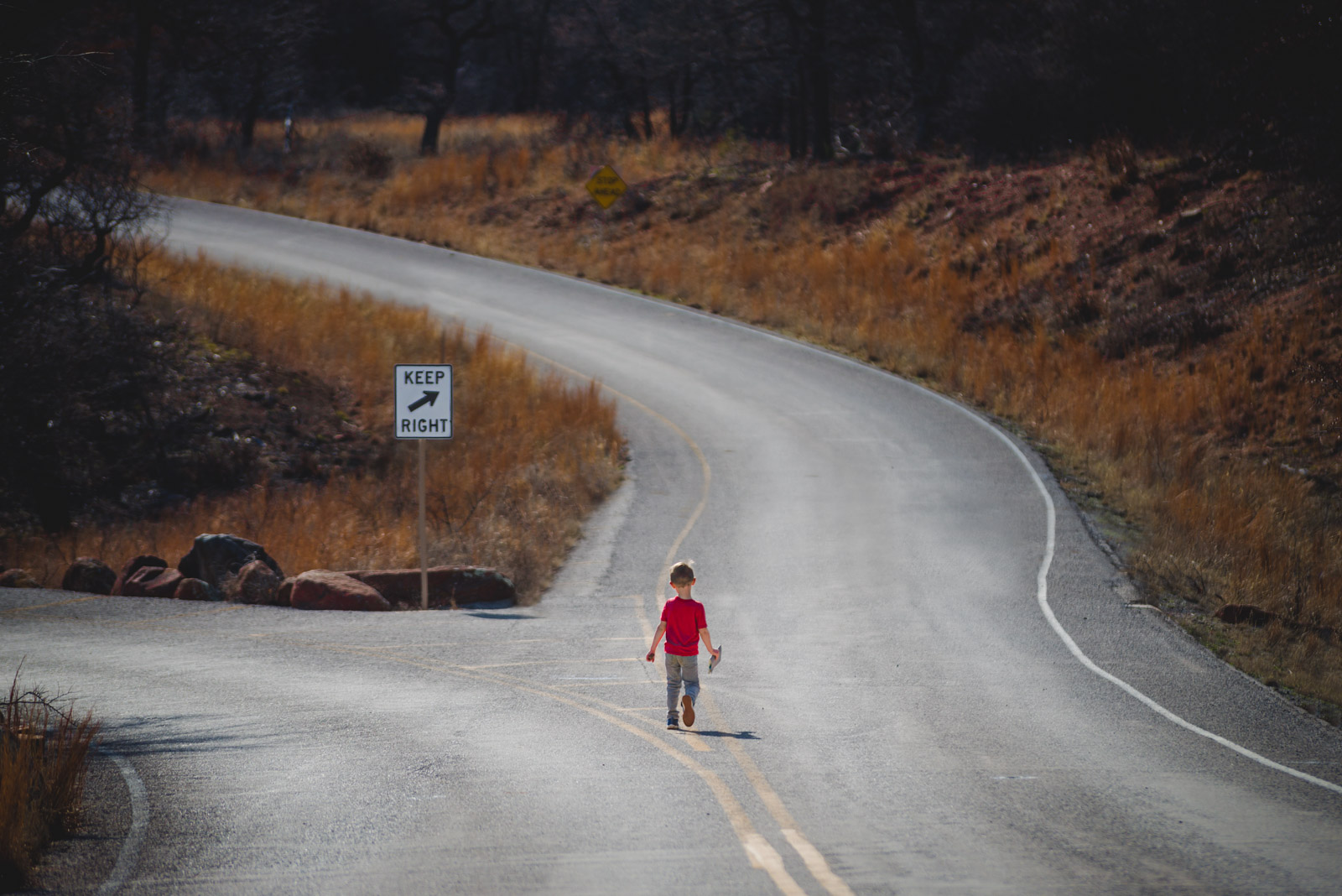 A boy meets a fork in the road, taking a break from photography
