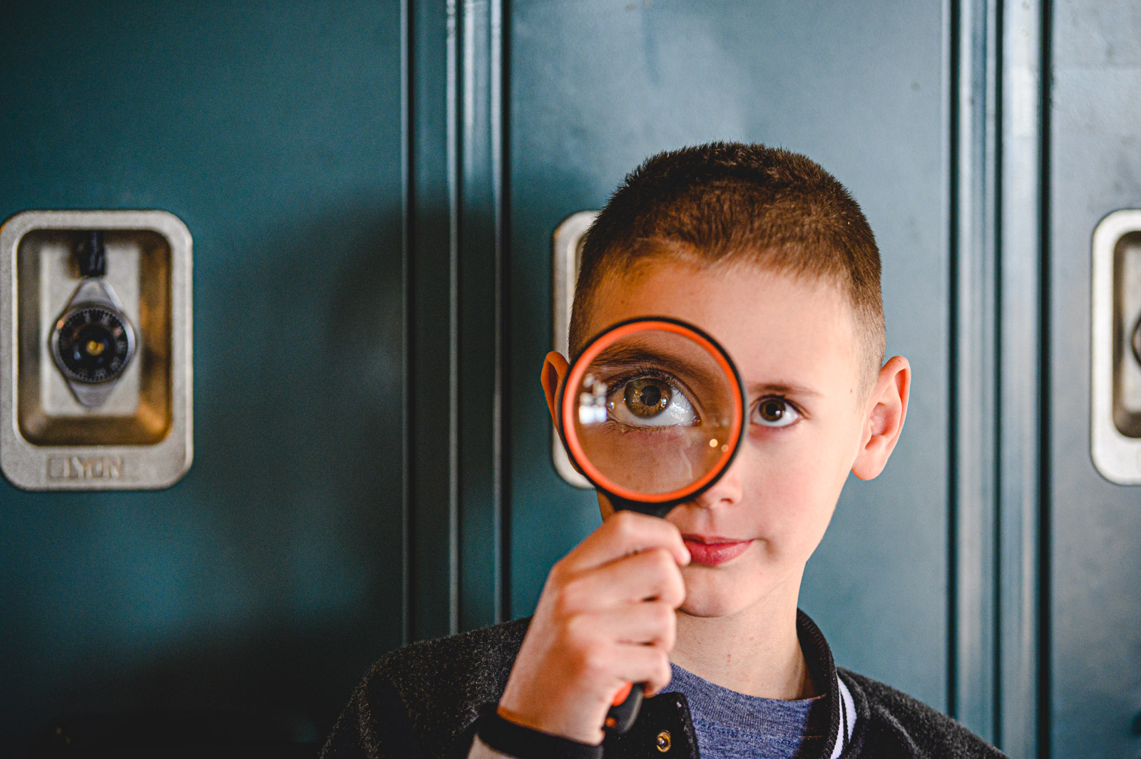 Boy with magnifying glass to his eye
