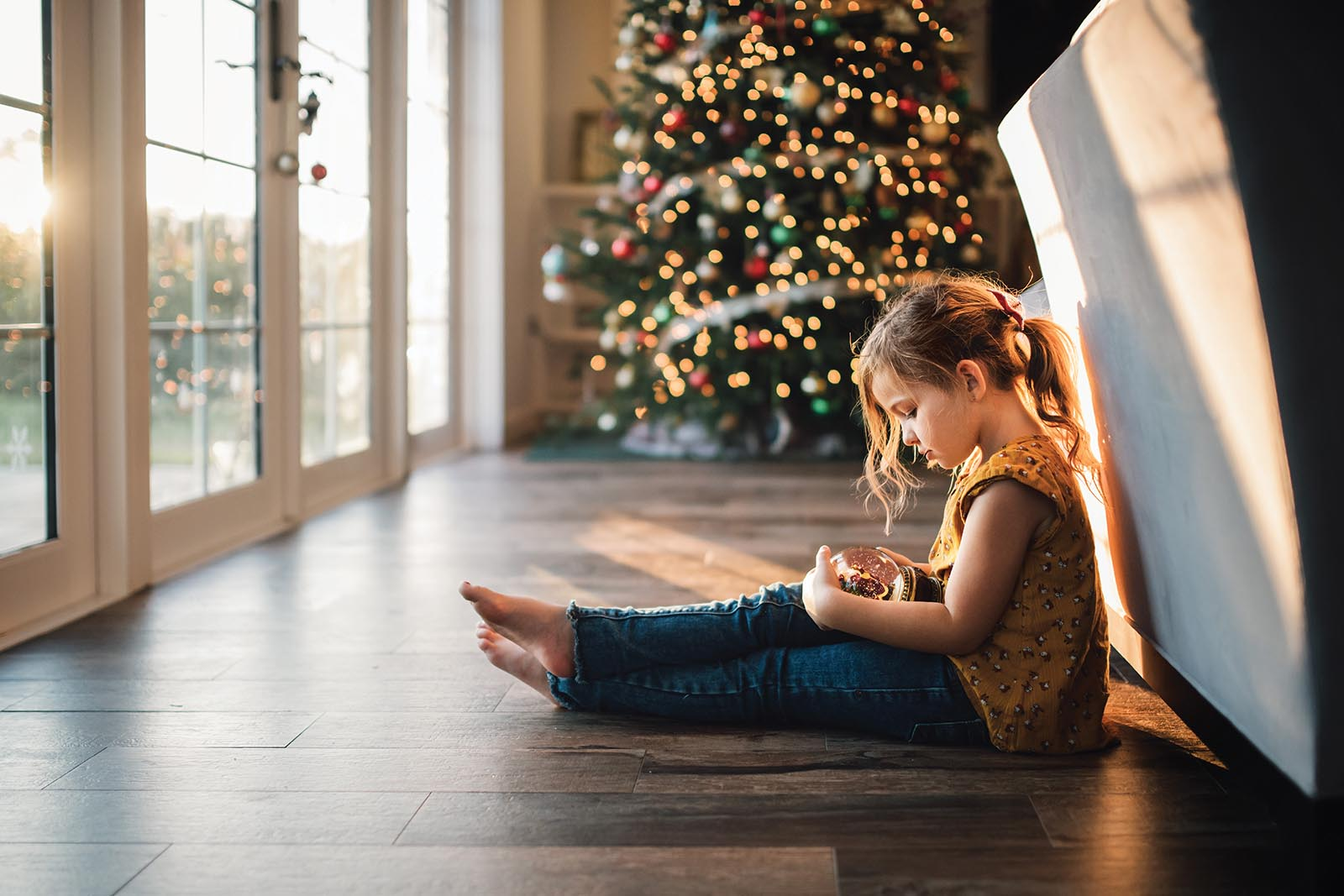 Girl sits in window light in front of Christmas tree