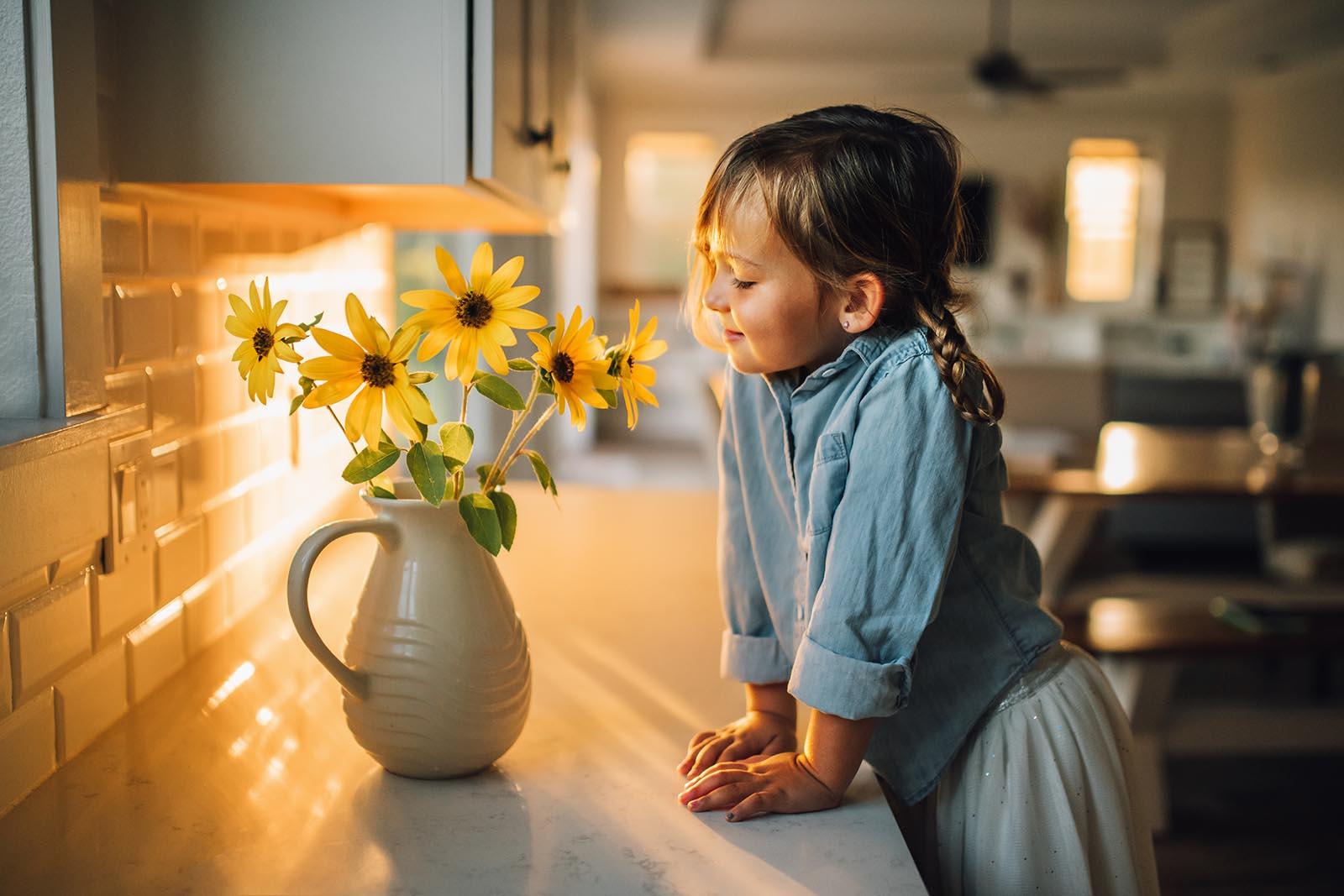 Girl in golden window light smells flowers