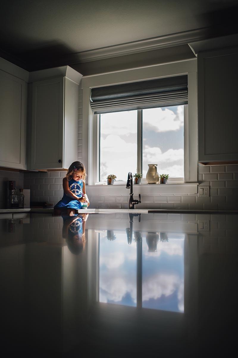 Pocket of light, girl sits in kitchen window light