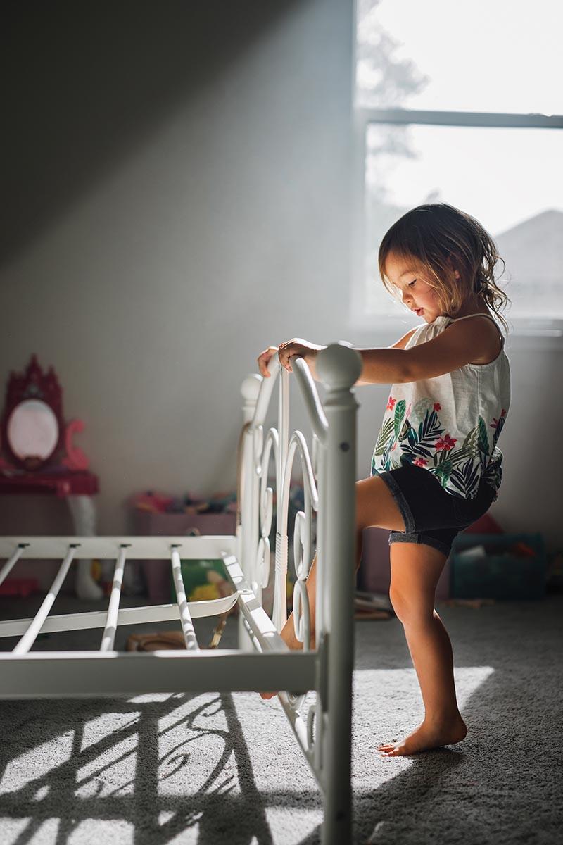 Girl plays in pocket of window light in bedroom