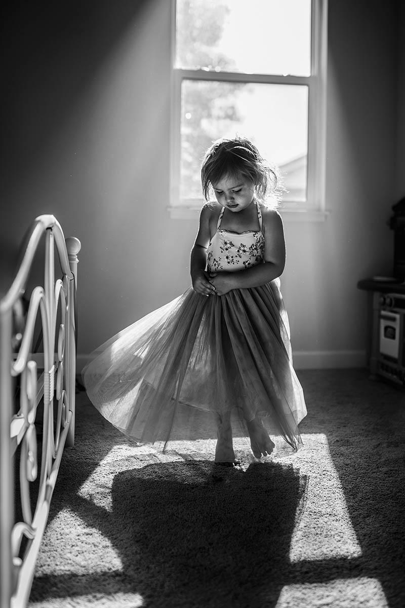 Girl twirls in pocket of window light