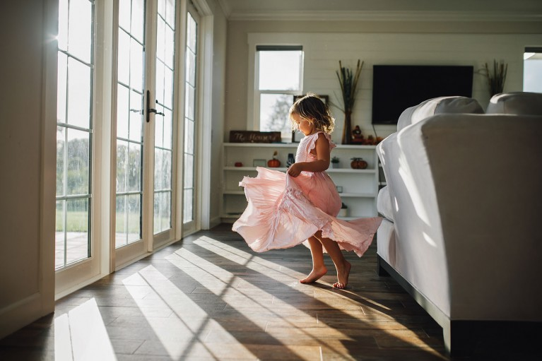 Creative use of window light, little girl twirling