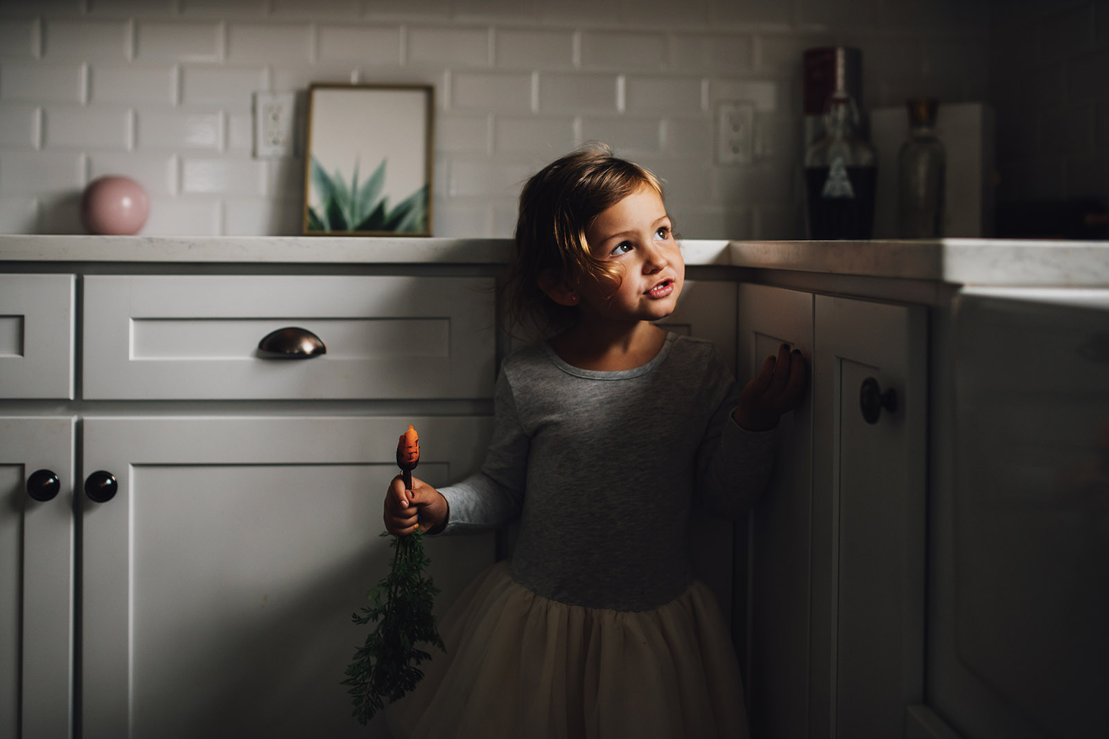 Creative use of window light, little girl in small pocket of kitchen light