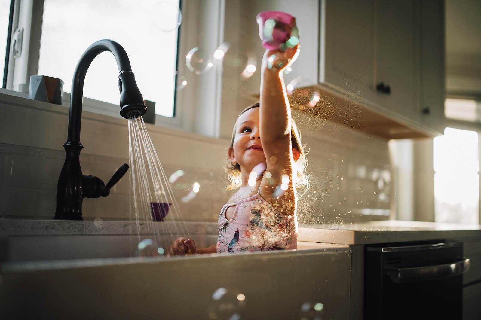 Girl plays bubbles in the sink near window light