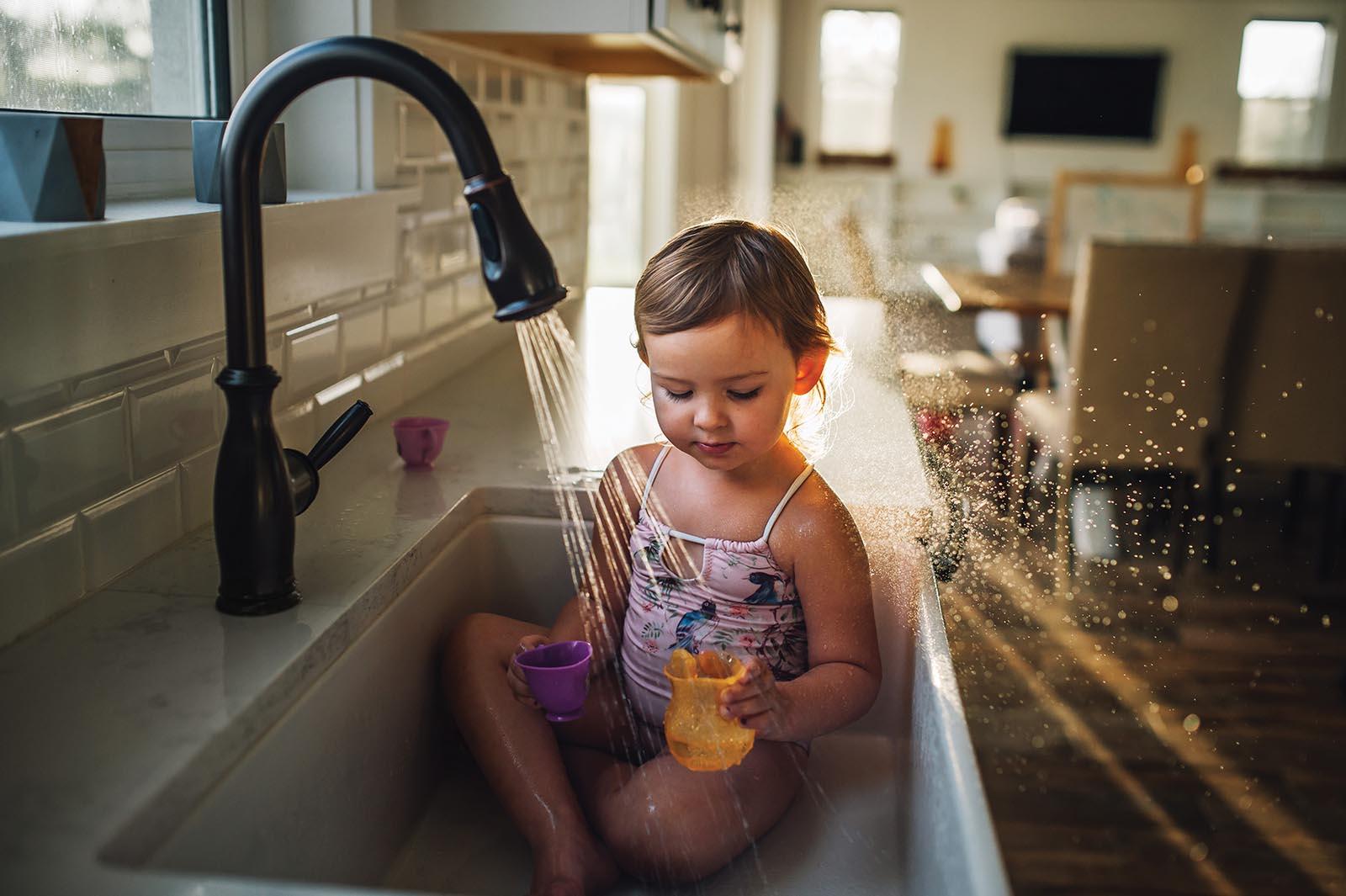Baby plays in sink in window light
