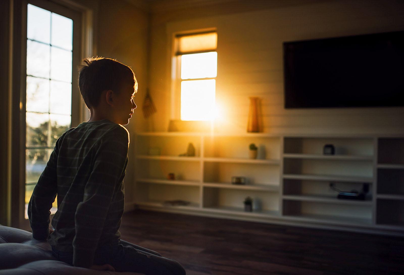 Golden sun flare through the window illuminates boy