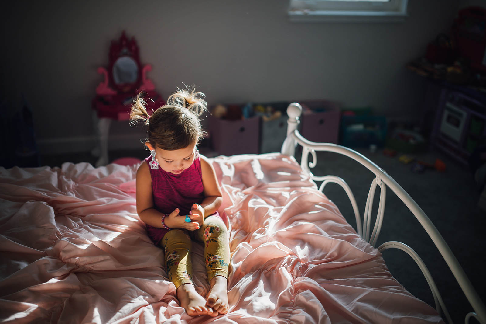 Girl sits on bed in pocket of window light