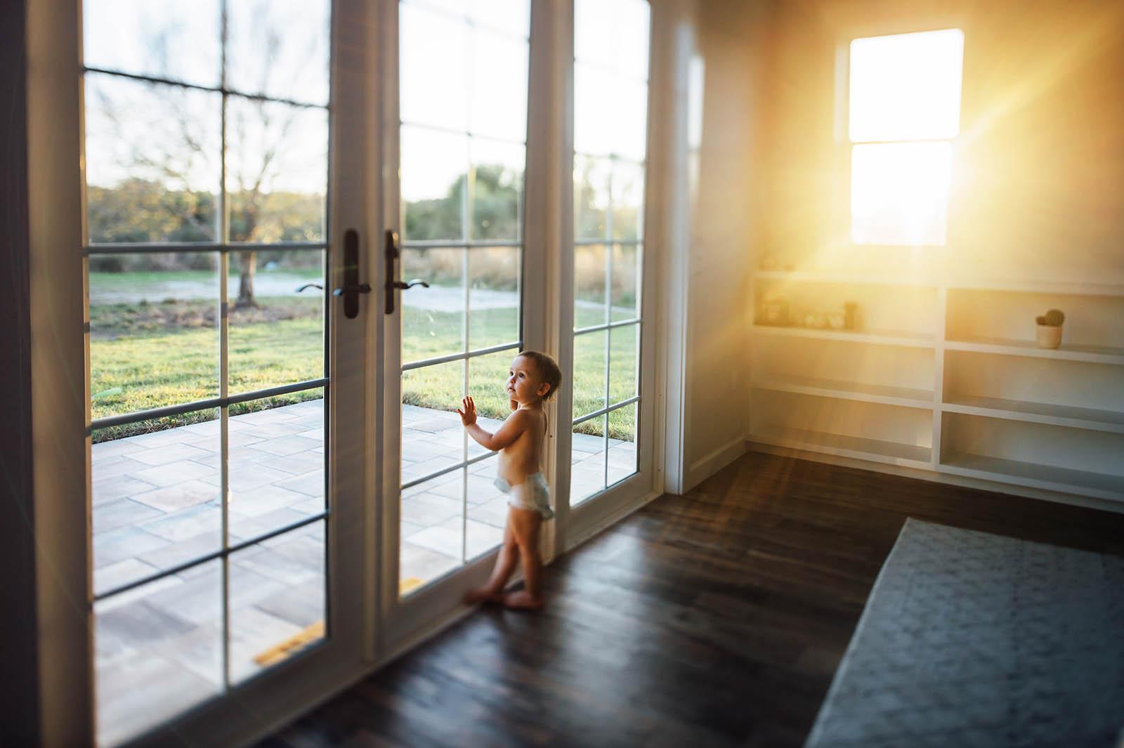 Window light sun flare as baby stands at door