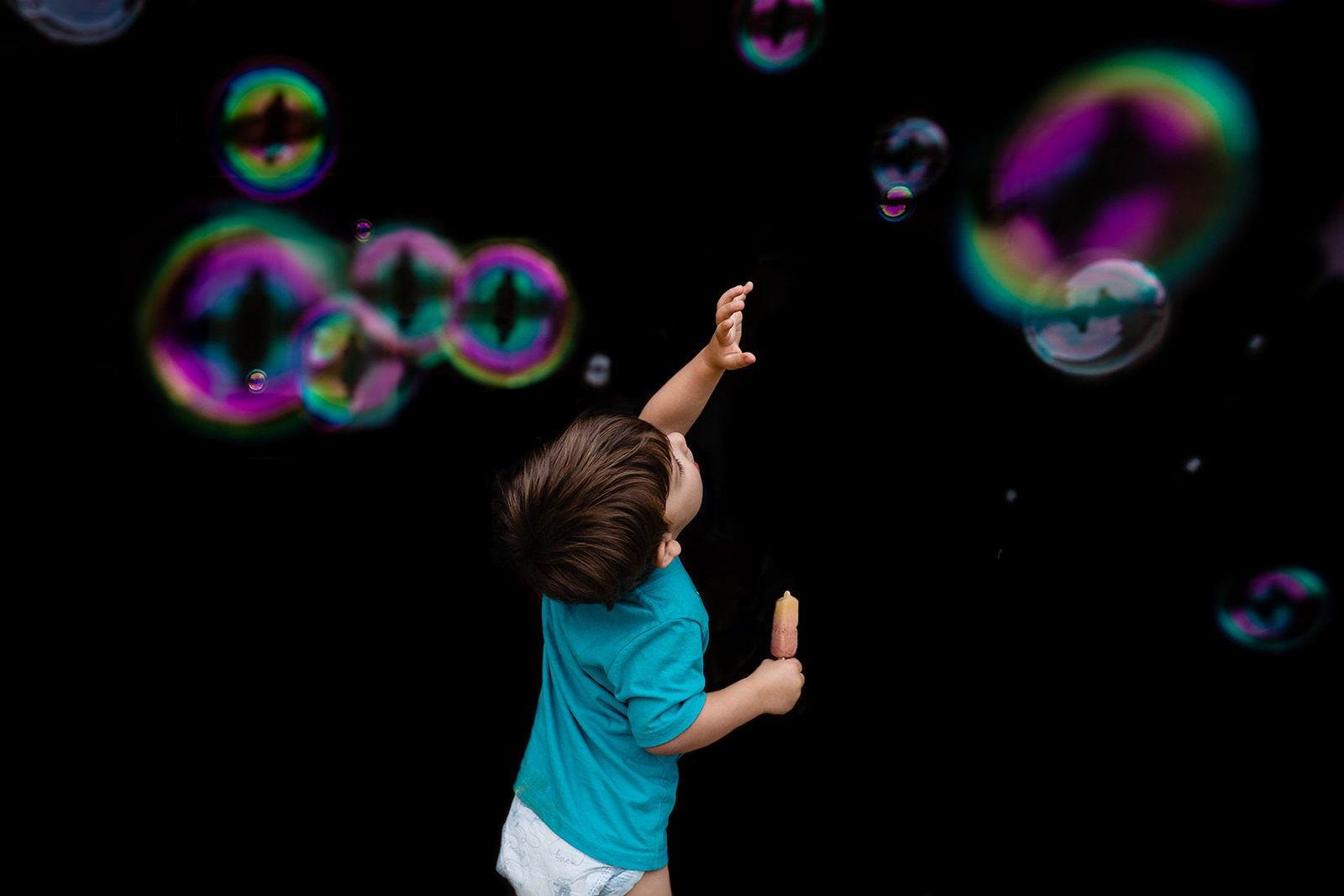 Toddler plays with bubbles in front of dark background