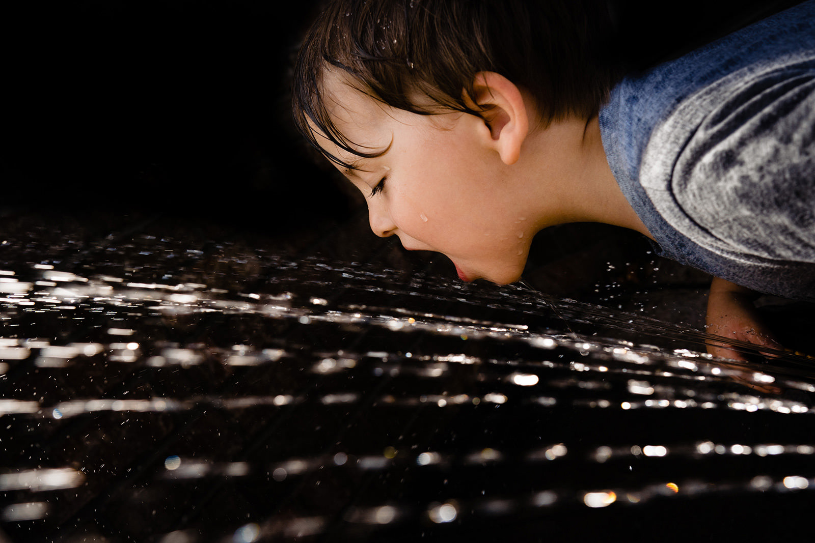 Boy drinks from hose during documentary family photos