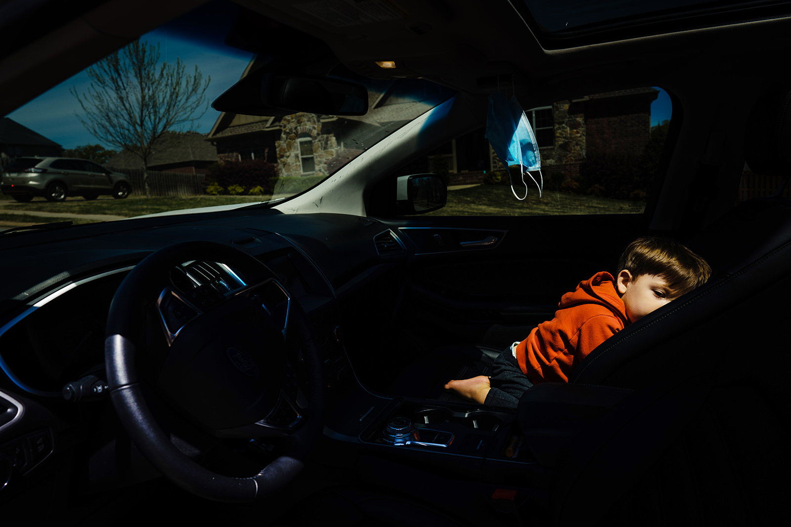 Documentary photo of a boy sleeping with parent in a dark car