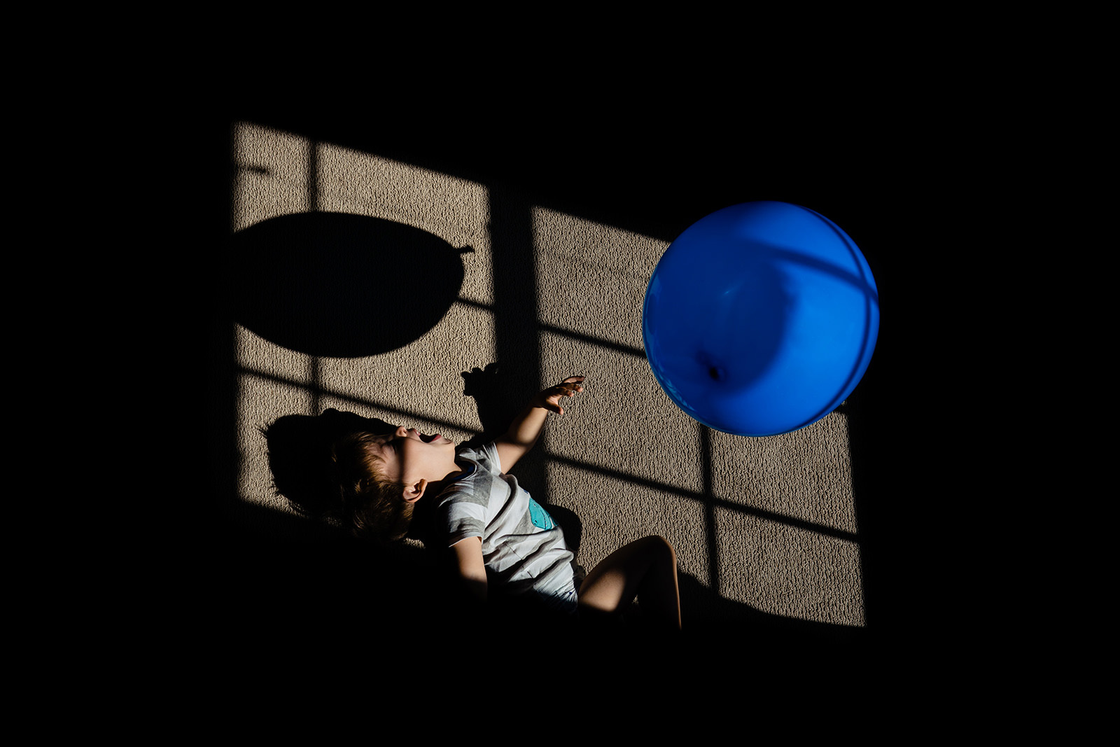 Toddler plays with balloon n dramatic window light during documentary photo session