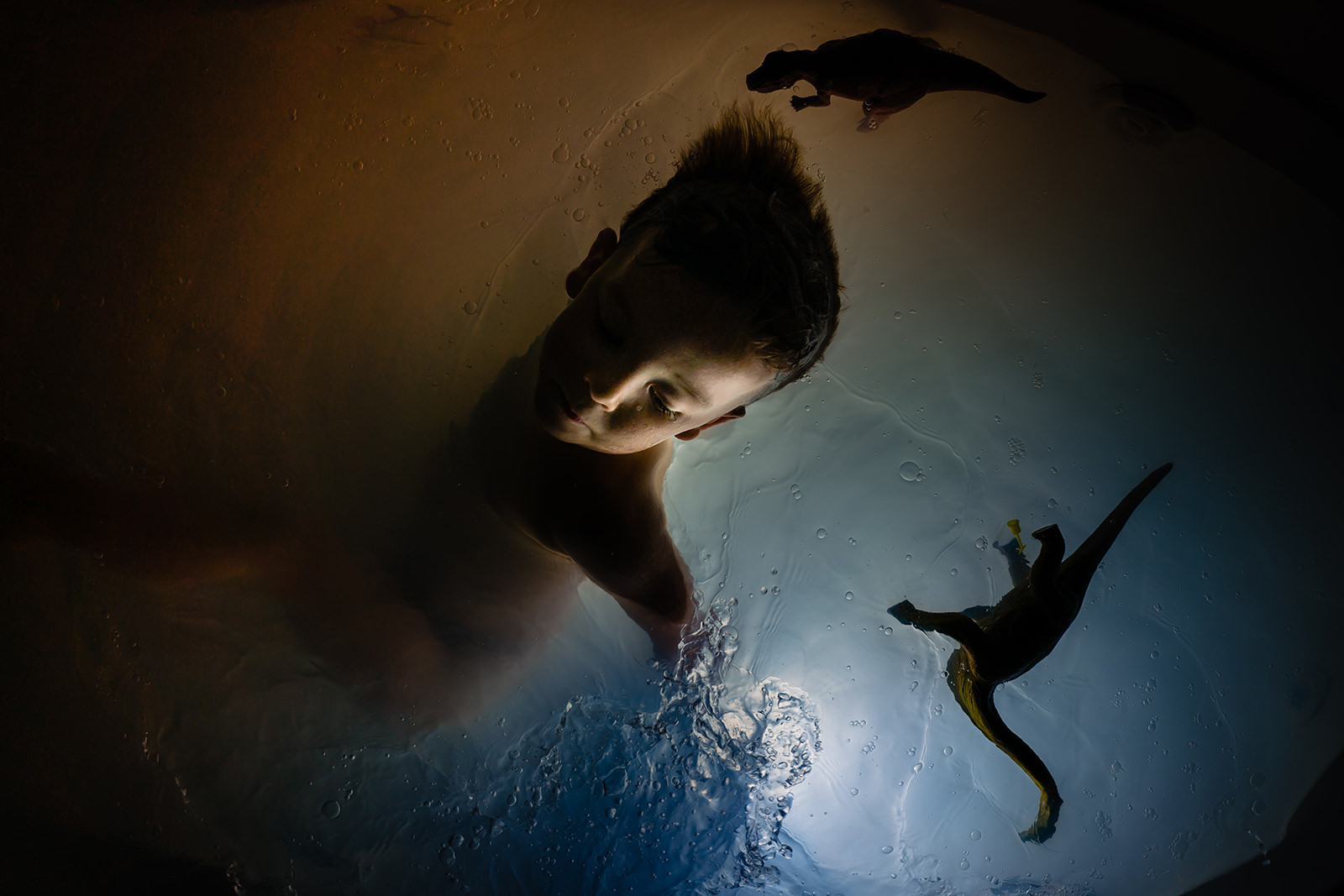 Boy in bathtub lit from below during documentary family photos