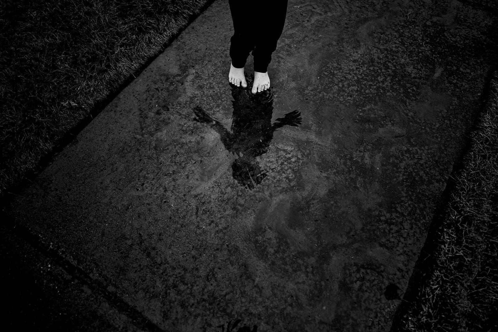 Black and white photo of a boy's feet and reflection during family documentary photos